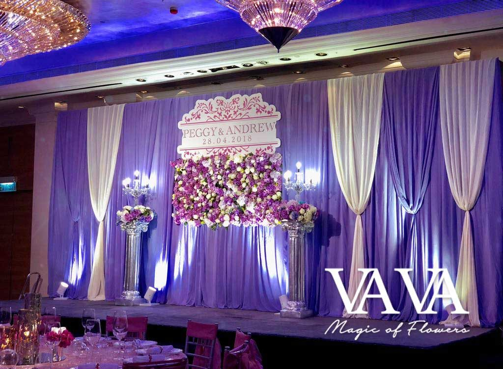 Purple curtain backdrop with flower arrangement at the ballroom